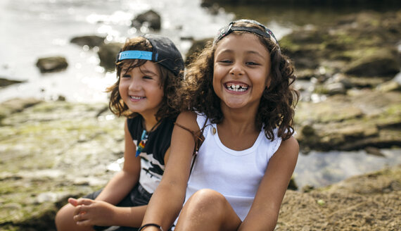 Spain, Gijon, portrait of smiling little girl and her friend in the background sitting at rocky coast - MGOF000544