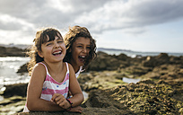 Spain, Gijon, portrait of two laughing little girls at rocky coast - MGOF000550