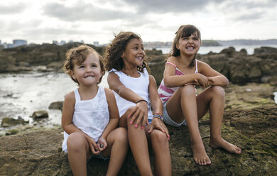Spain, Gijon, group picture of three little girls sitting at rocky coast - MGOF000562