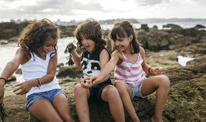 Spain, Gijon, group picture of three excited little children sitting at rocky coast - MGOF000564