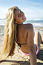 Portrait of smiling young woman on the beach looking over her shoulder - MGOF000568