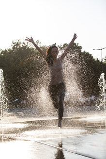 Woman running through fountain splashing water drops - FMKYF000626