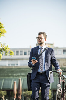 Young businessman pushing bicycle, holding smart phone - UUF005565