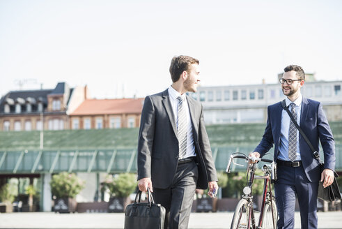 Two young businessmen walking in city, pushing bicycle - UUF005569