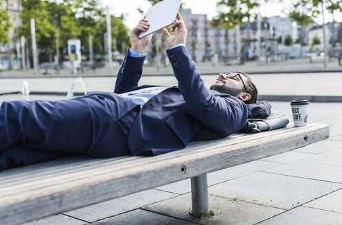 Young businessman lying on bench, working - UUF005586