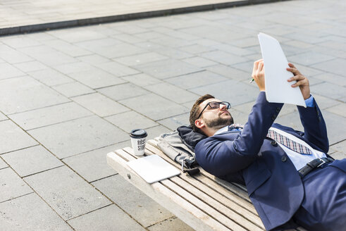 Young businessman lying on bench, working - UUF005588