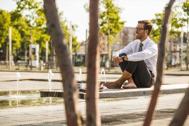 Young businessman sitting cross-legged on bench - UUF005597