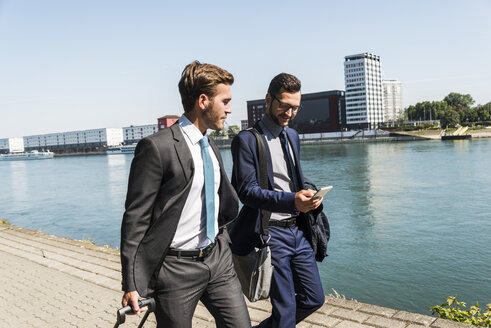 Two young businessmen on a business trip, walking by river - UUF005616
