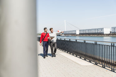 Two young businessmen walking by the riverside - UUF005622