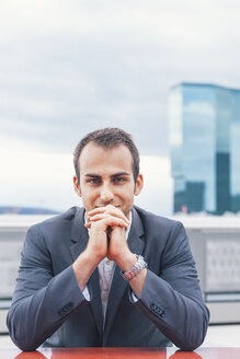 Portrait of confident businessman with hands on chin - BZF000222