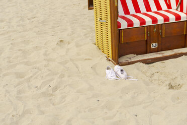 Pair of trainers and hooded beach chair on the beach - VIF000377