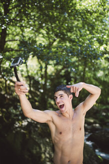 Shirtless young man making faces while filming himself with an action video camera - RAEF000396