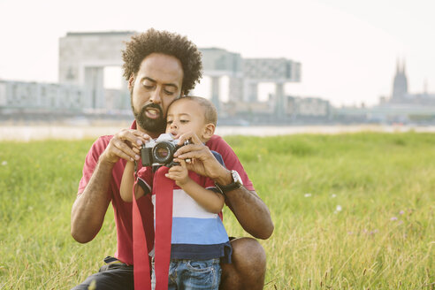 Germany, Cologne, father explaining camera to his son in a field - MADF000633