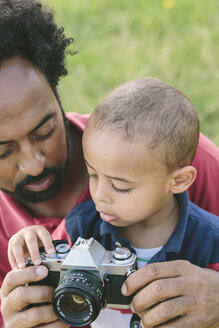 Father explaining camera to his son outdoors - MADF000635