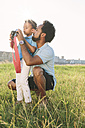 Germany, Cologne, father explaining camera to his son in a field - MADF000759