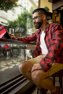 Adult bearded hipster style man touching tablet in bar and drinking alchohol near to window - JASF000016
