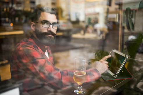 Adult bearded hipster style man touching tablet in bar and drinking alchohol near to window - JASF000018