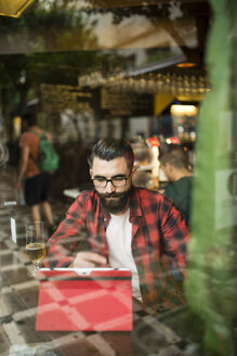 Adult bearded hipster style man touching tablet in bar and drinking alchohol near to window - JAS000021
