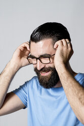 Portrait of smiling hipster with hands on his head in front of white background - JASF000024