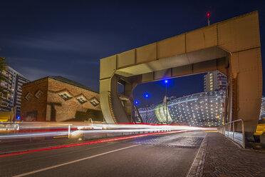 Germany, Bremerhaven, Klimahaus and lift bridge at night - NKF000381