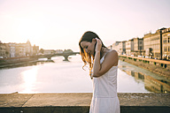 Italy, Florence, happy woman wearing white summer dress standing on a bridge at sunset - GEMF000327