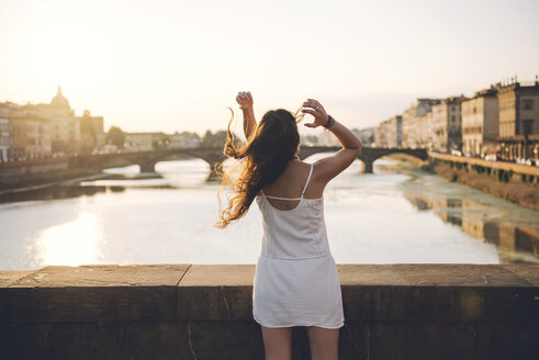 Italy, Florence, back view of woman wearing white summer dress standing on a bridge at sunset - GEMF000328