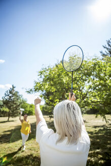 Two mature women on a meadow playing badminton - RKNF000183