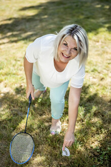 Smiling mature woman on a meadow playing badminton - RKNF000186