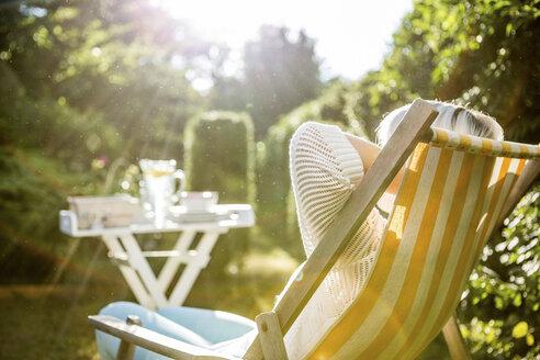 Mature woman relaxing in deckchair in garden - RKNF000226