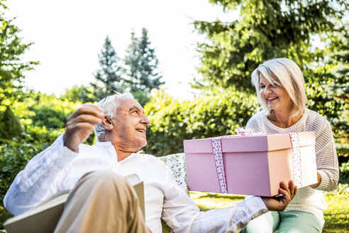 Happy elderly couple with large present outdoors - RKNF000359
