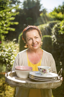 Mature woman carrying tray with dish set in garden - RKNF000243