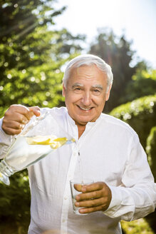 Smiling senior man pouring water in glass in garden - RKNF000246