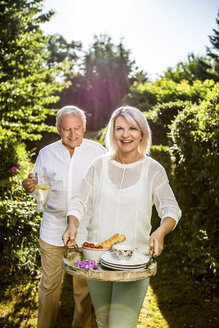 Elderly couple carrying carafe and tray in garden - RKNF000249