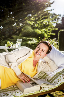 Smiling mature woman reading book on garden lounge - RKNF000255