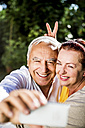 Playful elderly couple taking a selfie outdoors - RKNF000264