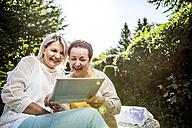 Happy mature women in garden with digital tablet - RKNF000273