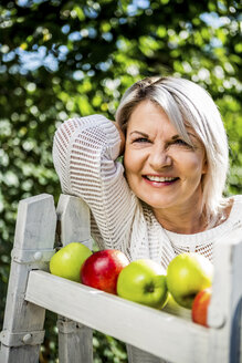 Smiling mature woman with apples outdoors - RKNF000283