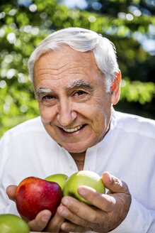 Smiling senior man holding apples outdoors - RKNF000287