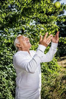Smiling senior man throwing an apple in garden - RKNF000288