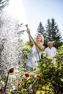 Smiling mature woman watering flowers in garden with man in background - RKNF000292