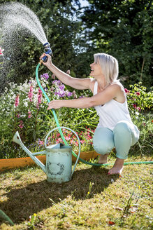 Smiling mature woman watering flowers in garden - RKNF000297