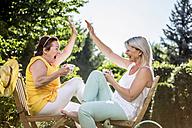 Happy mature women in garden high fiving - RKNF000304