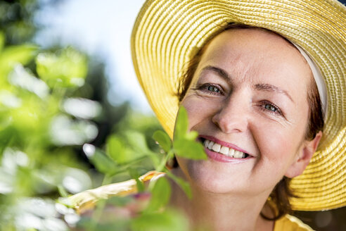 Portrait of smiling mature woman with herbs in garden - RKNF000311