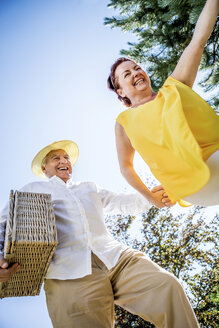 Happy elderly couple outdoors with picnic basket - RKNF000339
