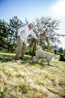 Senior man playing with dog on a meadow - RKNF000365
