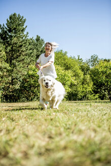 Happy mature woman with dog on a meadow - RKNF000369