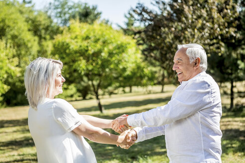 Happy elderly couple on a meadow - RKNF000342