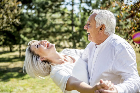 Happy elderly couple dancing outdoors - RKNF000349
