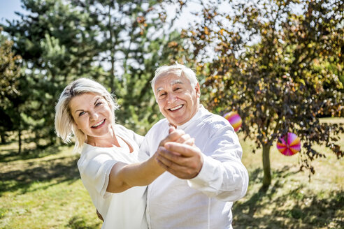 Happy elderly couple dancing outdoors - RKNF000351