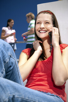 Happy young woman on cell phone in sunshine - TOYF001337
